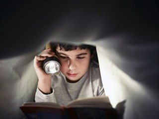young-boy-school-child-reading-book-at-night-under-PDGBM54-2