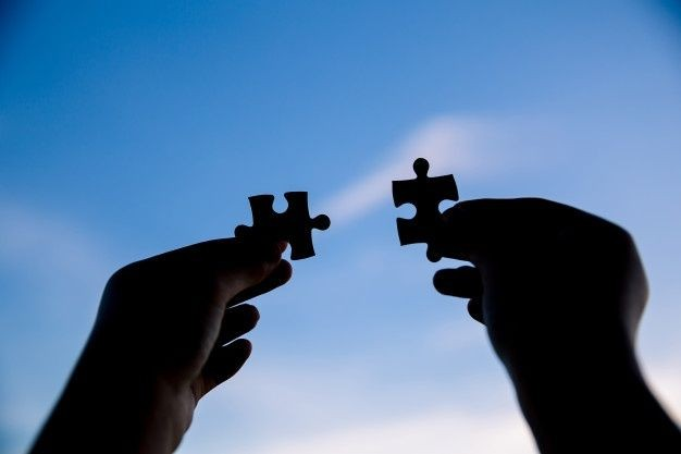 two-hands-trying-connect-couple-puzzle-piece-with-sunset-background_1150-17513